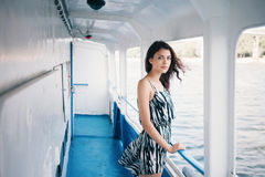 Young beautiful brunette woman in dress on the ship deck Stock Photo