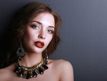 Young beautiful brunette woman in ear-rings, beads Stock Photography