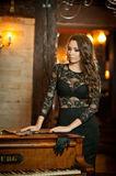 Young beautiful brunette woman in elegant black dress standing near a vintage piano. Sensual romantic lady with long dark hair Royalty Free Stock Photo