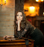 Young beautiful brunette woman in elegant black dress standing near a vintage piano. Sensual romantic lady with long dark hair Royalty Free Stock Images
