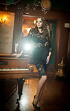 Young beautiful brunette woman in elegant black dress standing near a vintage piano. Sensual romantic lady with long dark hair Royalty Free Stock Image