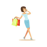 Young beautiful brunette woman in an elegant clothes walking with shopping bags and talking on mobile phone colorful Royalty Free Stock Photography