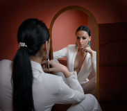 Young beautiful brunette woman in elegant white suit with trousers looking into large mirror. Seductive dark hair girl posing Royalty Free Stock Photos