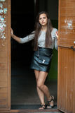 Young beautiful brunette woman in grey blouse black leather skirt and clutch standing in the doorway outdoors. Young beautiful brunette lady in grey blouse black Royalty Free Stock Photos