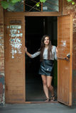 Young beautiful brunette woman in grey blouse black leather skirt and clutch standing in the doorway outdoors. Young beautiful brunette lady in grey blouse black Stock Image