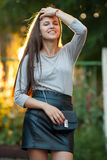 Young beautiful brunette woman in grey blouse black leather skirt and clutch standing in sunlight touching her hair with closed ey. Young beautiful brunette lady Royalty Free Stock Photo