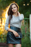 Young beautiful brunette woman in grey blouse black leather skirt and clutch standing in sunlight touching her hair outdoors. Young beautiful brunette lady in Royalty Free Stock Images