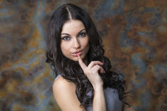 Young beautiful brunette woman has put forefinger to lips as sig Stock Image