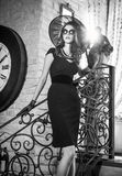 Young Beautiful Brunette Woman In Black Standing On Stairs Near An Over Sized Wall Clock. Elegant Romantic Mysterious Lady