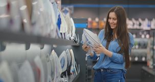 A young beautiful brunette woman inspects an iron in the store to buy a new apartment. A young beautiful brunette woman inspects an iron in the store to buy a stock video