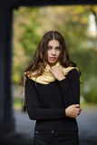 Young beautiful brunette woman with long wavy hair posing outdoors in black sweater and yellow scarf with blurry park background Stock Images
