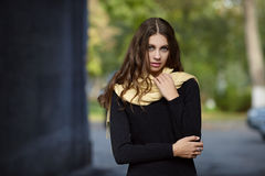 Young beautiful brunette woman with long wavy hair posing outdoors in black sweater and yellow scarf Stock Image