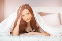 Young beautiful brunette woman looking out from coverlet Stock Photography