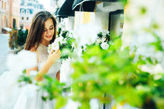 Young beautiful brunette woman looks at flowers on the street and breathes in their fragrance. Royalty Free Stock Photography
