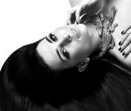 Young beautiful brunette woman lying on the floor wear expensive gold  crocodile jewellery with long hair Stock Images