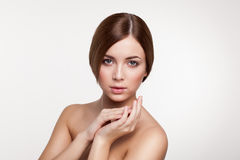 Young beautiful brunette woman with natural makeup on grey backg Stock Photos
