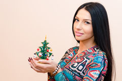 Young beautiful brunette woman pinup girl with little Christmas toy tree in hands happy smiling & looking at camera on Royalty Free Stock Image