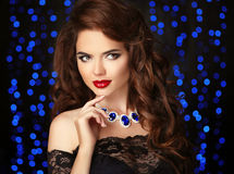 Young beautiful brunette woman portrait. Red lips makeup. Curly. Hair style. Fashion gems necklace jewelry. Attractive female over party lights background Royalty Free Stock Photo