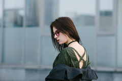Young beautiful brunette woman posing at the camera exposing their backs against the backdrop of modern architecture. Young stylish brunette woman wearing Stock Images