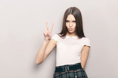 Young beautiful brunette woman posing indoors against wall with air kiss and v gesture Stock Photography