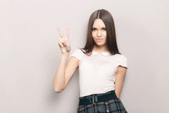 Young beautiful brunette woman posing indoors against wall with v gesture Stock Images