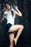 Young beautiful brunette woman posing in wet fashionable clothes Royalty Free Stock Images