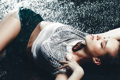 Young beautiful brunette woman posing in wet fashionable clothes Stock Photo