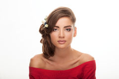 Young beautiful brunette woman in red blouse with low bun hairstyle and flower headpiece showing adorable makeup Stock Photography