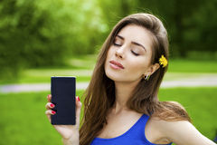 Young beautiful brunette woman shows a new smart phone Royalty Free Stock Photo