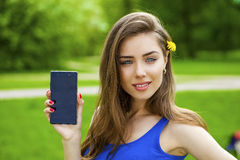 Young beautiful brunette woman shows a new smart phone Royalty Free Stock Image