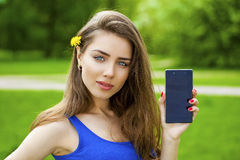 Young beautiful brunette woman shows a new smart phone Royalty Free Stock Photos