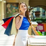 Happy brunette woman with some red shopping bag. Young beautiful brunette woman with some red shopping bag in the mall royalty free stock image