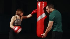 Young beautiful brunette woman in sportswear is training with his Boxing coach. Holds punches with Boxing gloves in. Pouch on black background stock video footage