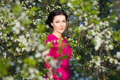 Young beautiful brunette woman standing near the cherry tree Stock Photos