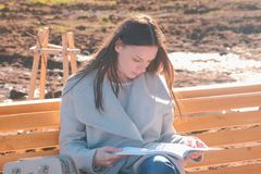 Young beautiful brunette woman student sits on the bench in spring park, reads a book. stock photo