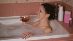Young beautiful brunette woman takes a bath, drinks whiskey and smiling. stock footage