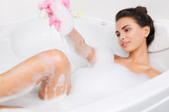 Beautiful young woman takes bubble bath Stock Images