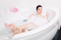 Beautiful young woman takes bubble bath Royalty Free Stock Images