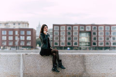 Young beautiful brunette woman talking on cell telephone while relaxing after walking in urban setting, Royalty Free Stock Images