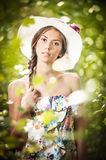 Young beautiful brunette woman wearing a large hat in a sunny day.. Portrait of attractive long hair female with multicolored blouse, outdoor shot in a garden Royalty Free Stock Photography