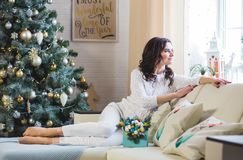 Young beautiful brunette woman wearing white knitted sweater at home by the window. Young beautiful brunette woman sitting on th ewhite sofa wearing white stock photos