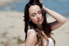 Young beautiful brunette woman in white dress on the seashore. portrait with closed eyes Stock Photo