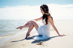 Young beautiful brunette woman in white dress on the seashore. Sitting on the sand Royalty Free Stock Images