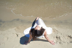 Young beautiful brunette woman in white dress on the seashore, sitting on the sand. Top view Royalty Free Stock Photo