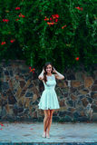 Young beautiful brunette woman in white dress stands on stone wall background with green leaves and flowers. Royalty Free Stock Photography