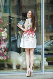 Young beautiful brunette woman in white flowers dress walking on Stock Images