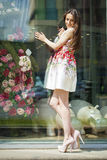 Young beautiful brunette woman in white flowers dress walking on Stock Image