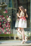 Young beautiful brunette woman in white flowers dress walking on Royalty Free Stock Photos