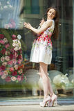 Young beautiful brunette woman in white flowers dress walking on Stock Photo