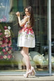 Young beautiful brunette woman in white flowers dress walking on Stock Photos